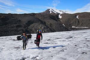 Tom Bishop and James O'Dwyer carry the sUAV system onto the glacier.